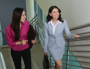 Two business women walking up staircase in office building, elevated view