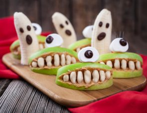 Funny halloween eadible monsters scary food healthy vegetarian snack dessert recipe for party decoration. Homemade spooky cyclop apples with teeth and banana ghosts on vintage wooden background. Natural treat