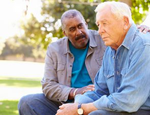 Man Comforting Unhappy Senior Friend Outdoors Sitting On A Bench