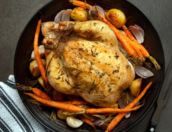 Roasted chicken dinner with vegetables and herbs.  Overhead view.